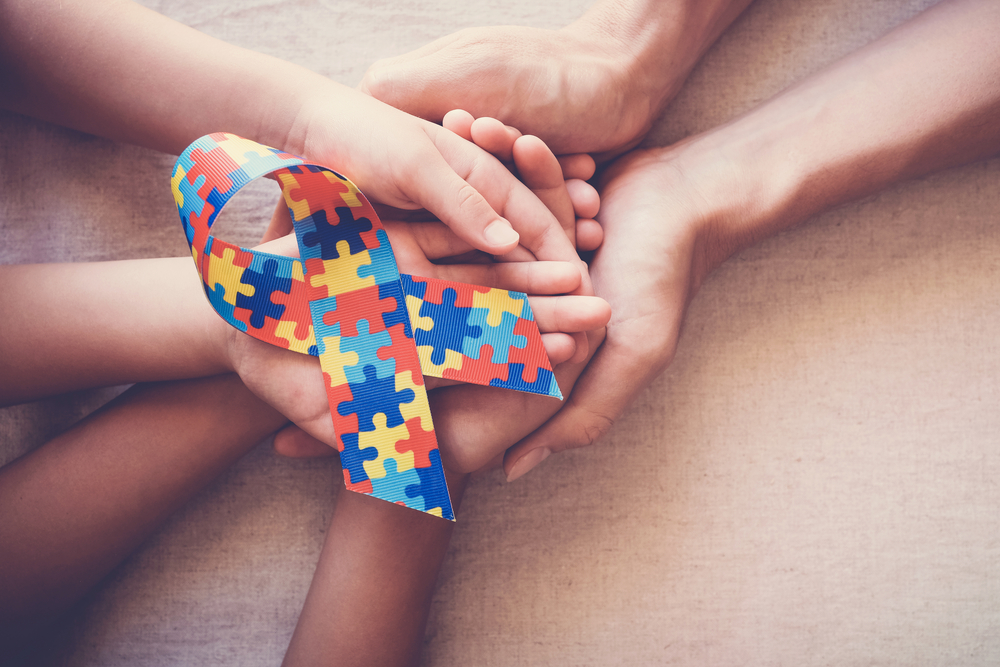 family holding Autism Awareness ribbon